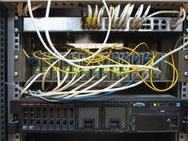 A cremalheira do servidor com cabos do cabo de remendo do Internet conectou ao painel fotografia de stock royalty free