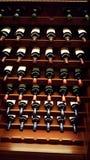 Cremalheira do vinho com as garrafas que refletem grânulos da luz Fotografia de Stock