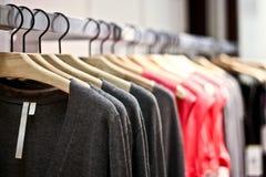 Cremalheiras das camisolas e das camisas que penduram em uma loja imagens de stock royalty free