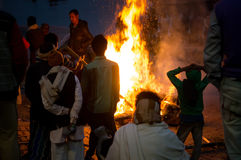 Cremation ceremony in Manikarnika Ghat on the Ganges River in Varanasi, People look at the funeral pyre Royalty Free Stock Photos