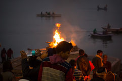 Cremation ceremony in Manikarnika Ghat on the Ganges River in Varanasi, People look at the funeral pyre Royalty Free Stock Images