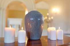 Cremation urn and candles burning in church Stock Photos