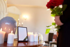 Cremation urn and woman at funeral in church. Cremation, people and mourning concept - cinerary urn, photo frame with black ribbon and woman holding red roses at stock photos