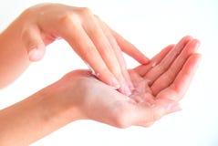 Creme auf Frauenhand mit lokalisiertem Hintergrund Lizenzfreie Stockbilder