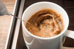 Creme batendo no café em um copo branco no fogão na cozinha para alcançar o crema no café da manhã fotografia de stock royalty free