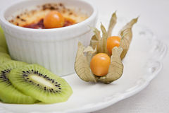 Creme brulee. With kiwi and physalis Royalty Free Stock Image