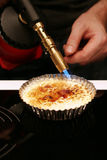 Creme brulee with blowtorch. Chef caramelizes sugar on creme brulee with cooking torch Stock Images