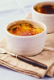 Creme brulee. On a blue table Royalty Free Stock Photography