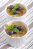 Creme brulee with blueberries and mint Stock Photos