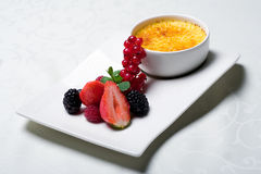 Creme Brulee - delicious dessert. Traditional french cuisine - originally decorated creme brulee with fresh berries Royalty Free Stock Photos