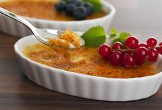 Creme brulee dessert in bowl and on spoon Stock Photos