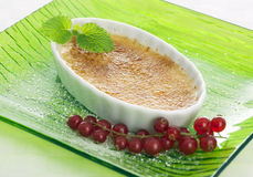 Creme brulee dessert with red currant Stock Image