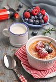 Creme brulee with raspberry, blueberry and rosemary with ingredi. Creme brulee with raspberry, blueberry and rosemary in white ramekin with ingredients and Royalty Free Stock Photos