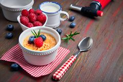 Creme brulee with raspberry, blueberry and rosemary with ingredi. Creme brulee with raspberry, blueberry and rosemary in white ramekin with ingredients and Stock Photos