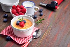 Creme brulee with raspberry, blueberry and rosemary with ingredi. Creme brulee with raspberry, blueberry and rosemary in white ramekin with ingredients and Stock Photo