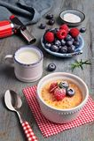 Creme brulee with raspberry, blueberry and rosemary with ingredi. Creme brulee with raspberry, blueberry and rosemary in white ramekin with ingredients and Stock Image