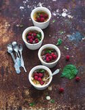 Creme brulees with raspberries and mint in white Stock Photography