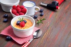 Creme brulle με το σμέουρο, το βακκίνιο και το δεντρολίβανο με το ingredi Στοκ Εικόνες
