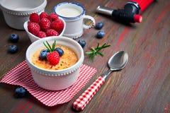 Creme brulle με το σμέουρο, το βακκίνιο και το δεντρολίβανο με το ingredi Στοκ Φωτογραφίες