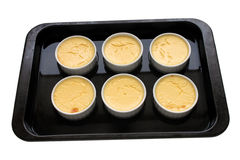 Creme Caramel In A Bain Marie. Cooked creme caramel in an isolated bain marie Stock Images