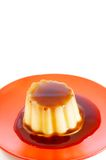 Creme caramel on red plate. Creme caramel dessert shot on red plate on white background Stock Photography