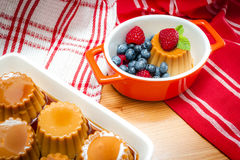 Creme caramel served with sweet syrup and fresh berries Royalty Free Stock Image