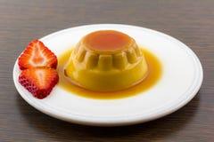 Creme caramel vanilla custard dessert or flan on white dish with Stock Image