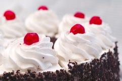 Creme chicoteado no bolo com as cerejas de um cocktail Imagens de Stock