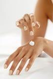 Creme da mão Feche acima das mãos da mulher que aplicam a loção na pele Fotos de Stock Royalty Free