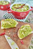 Creme das ervilhas espalhadas em fatias do pão Imagens de Stock