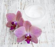 Creme de cara com flores das orquídeas fotos de stock