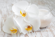 Creme de cara com flores das orquídeas foto de stock