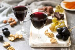 Creme de Cassis homemade liqueur served with grapes, nuts and chocolate. Rustic style. stock images