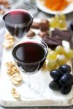 Creme de Cassis homemade liqueur served with grapes, nuts and chocolate. Rustic style royalty free stock photos