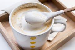 Creme de chicoteamento em uma colher e em um cappuccino da xícara de café Imagens de Stock