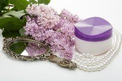 Creme e flores cosméticos do lilás Fotografia de Stock