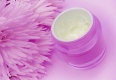 Creme e flores faciais na cor-de-rosa Fotos de Stock Royalty Free
