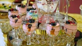 Creme e souffle coloridos da sobremesa do fruto da tabela de Furshet do feriado no vidro projeto comemorativo do alimento do jant vídeos de arquivo