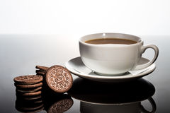 Creme-filled sandwich cookie and coffee on dark reflective background. Stock Photography