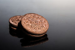 Creme-filled sandwich cookie on dark reflective background Royalty Free Stock Image