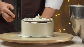 Creme nivelado do cozinheiro chefe no bolo com souffle de queijo com uma espátula filme