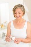 Creme sênior da almofada de algodão da preensão do banheiro da mulher Fotografia de Stock Royalty Free