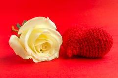 Creme stieg mit roter Herzhäkelarbeit auf rotem Hintergrund Lizenzfreie Stockbilder
