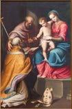 CREMONA ITALIEN, 2016: Målningen av den heliga familjen med Stet Nicholas i kyrkliga Chiesa di Santa Agata av Bernardino Campi Royaltyfri Fotografi