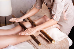 Creole massage with bamboo sticks. Woman having anti-stress massage with bamboo sticks Royalty Free Stock Photography