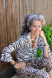 Creole woman smiling exotic outfit outdoor. Exotic dressed smiling Creole woman sitting outdoor. Bamboo fence and plants in the background. Open shade stock image