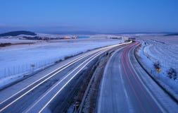 Crepúsculo de la mañana y rastros de los coches en la carretera Foto de archivo libre de regalías