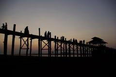 Crepúsculo en el puente de U-Ben con la gente de myanmar Foto de archivo libre de regalías