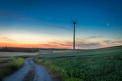 Crepúsculo impressionante sobre o campo e turbinas eólicas verdes Fotos de Stock