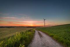 Crepúsculo impressionante sobre o campo e turbinas eólicas verdes no verão fotos de stock royalty free